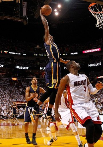Paul George of the Indiana Pacers dunks over Dwyane Wade of the Miami Heat
