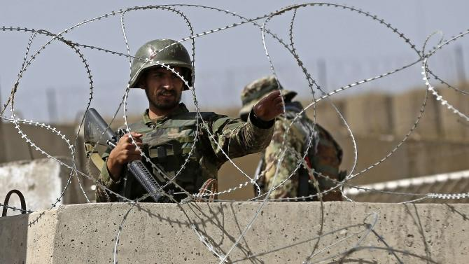 Afghan National Army soldier keeps watch at gate of a British-run military training academy Camp Qargha, in Kabul