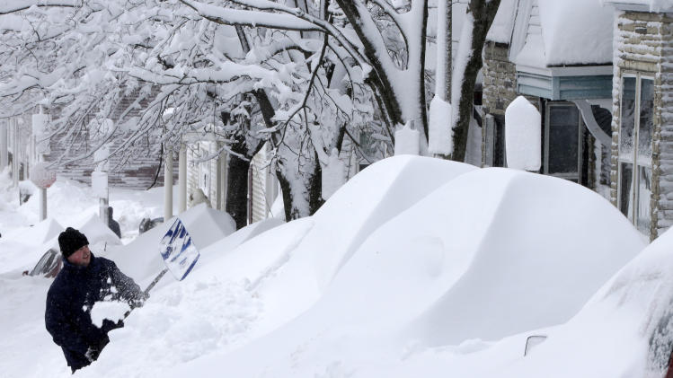 A man shovels snow off his car in front of his home on East Third street in the South Boston neighborhood in Boston, Saturday, Feb. 9, 2013.  A howling storm across the Northeast left the New York-to-Boston corridor shrouded in 1 to 3 feet of snow Saturday, stranding motorists on highways overnight and piling up drifts so high that some homeowners couldn't get their doors open. More than 650,000 homes and businesses were left without electricity. (AP Photo/Gene J. Puskar)