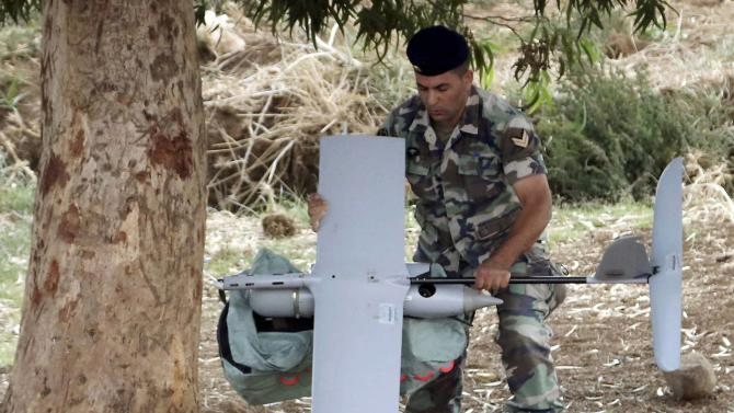 Lebanese Army soldier carries an Israeli drone in the Marjeyoun countryside, south Lebanon
