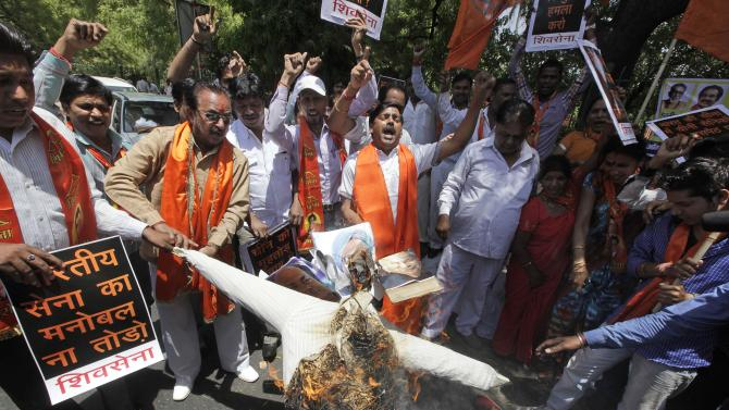 Indian protesters of right wing Shiv Sena party burn an effigy with photographs of India Defense Minister A.K.Antony, left, Prime Minister Manmohan Singh, center  and Home Minister Sushil Kumar Shinde  during a protest against the alleged incursion by Chinese troops into Indian territory in New Delhi, India, Wednesday, May 1, 2013. India said Chinese troops crossed the de facto border between the countries and went 10 kilometers (six miles) into Indian territory on April 15. About 50 Chinese soldiers were camping in tents Kashmir's Ladakh region.  (AP Photo /Manish Swarup)