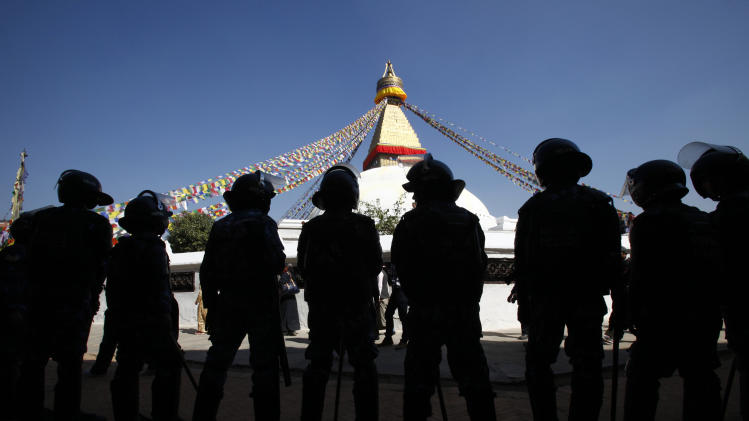 Nepalese policemen stand guard near Boudhanath Stupa during the third day of Tibetan New Year in Katmandu, Nepal, Wednesday, Feb. 13, 2013. A Tibetan protester doused himself with gasoline and set himself on fire in Nepal's capital Wednesday, the latest self-immolation to protest Chinese rule in Tibet. (AP Photo/Niranjan Shrestha)