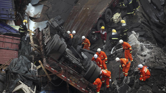 CORRECTS DATE - Rescuers work at the accident site where an expressway bridge partially collapsed due to a truck explosion in Mianchi County, Sanmenxia, central China's Henan Province, Friday, Feb. 1, 2013. A truckload of fireworks intended for Lunar New Year celebrations went off Friday in a massive, deadly explosion that destroyed part of an elevated highway in central China, sending vehicles plummeting 30 meters (about 100 feet) to the ground. (AP Photo) CHINA OUT