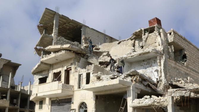Men work on a damaged building in order to rebuild it at al-Hamidiya area, after rebel fighters took control of the area from forces loyal to Syria's President Bashar al-Assad earlier this month in the northwestern province of Idlib