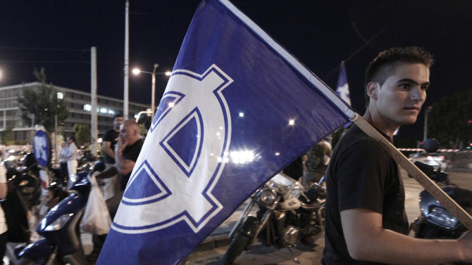 Supporters of the far right party of Golden Dawn  celebrate the results of the elections outside their headquarters office in Thessaloniki, Greece Sunday, June 17, 2012. Official projections showed the Golden Dawn party returning to the 300-member parliament with 18 seats, just three fewer than it had won in an inconclusive election on May 6, when no party won enough votes to form a government amid a deep financial crisis that threatens Greece's place in the Eurozone and could hurt the global economy. The pro-bailout New Democracy party came in first Sunday in Greece's national election, and its leader has proposed forming a pro-euro coalition government. (AP Photo/Dimitri Messinis)