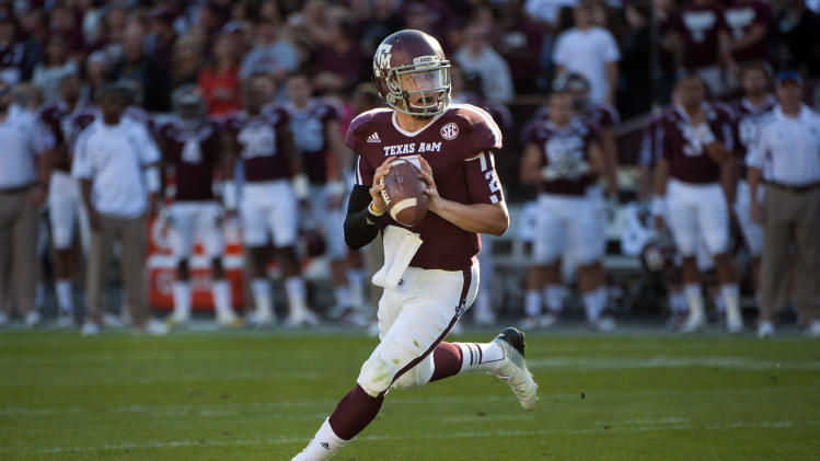 FILE - In this Nov. 17, 2012, file photo, Texas A&M's Johnny Manziel rolls out to throw a touchdown pass during the first quarter of an NCAA college football game against Sam Houston State in College Station, Texas. Manziel has become the first freshman to be voted The Associated Press Player of the Year in college football, Tuesday, Dec. 18, 2012.  (AP Photo/Dave Einsel, File)
