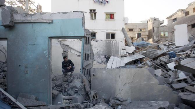 A Palestinian man sits in the rubble of a destroyed house after an Israeli airstrike in the Jabaliya refugee camp, northern Gaza Strip, Sunday, Nov. 18, 2012. The Israeli military widened its range of targets in the Gaza Strip on Sunday to include the media operations of the Palestinian territory's Hamas rulers, sending its aircraft to attack two buildings used by both Hamas and foreign media outlets. (AP Photo/Hatem Moussa)