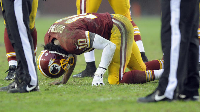 Washington Redskins quarterback Robert Griffin III kneels on the ground after an injury during the second half of an NFL football game against the Baltimore Ravens in Landover, Md., Sunday, Dec. 9, 2012. (AP Photo/Nick Wass)