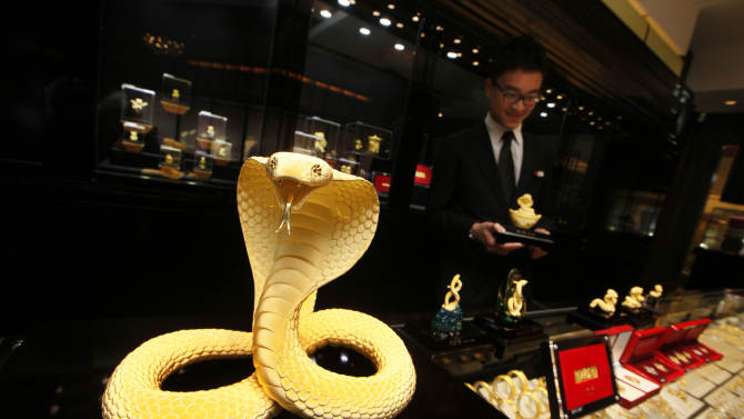 FILE - In this Jan. 18, 2013 file photo, an assistant shop clerk works near a newly unveiled gold snake on display for sale ahead of the upcoming Chinese lunar new year, the year of the Snake, at a jewelry shop in Hong Kong. The 380 gram-gold snake is for sale at HK$200,000 (US$25,800). Chinese New Year remains the most important festival in the region, a weeklong round of family reunions, temple visits, and gastronomic excess.   (AP Photo/Kin Cheung, File)