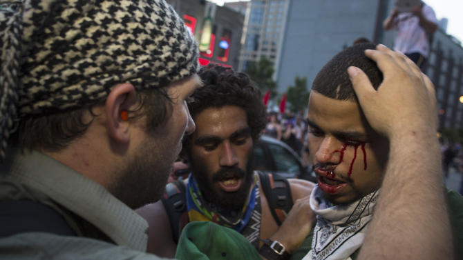 A bleeding anti-NATO protestor is comforted after a scuffle with police during a march, Saturday, May 19, 2012, in Chicago. On Sunday, the start of the two-day NATO summit, thousands of protesters are expected to march to the McCormick Place convention center, where NATO delegates will be meeting. (AP Photo/John Minchillo)