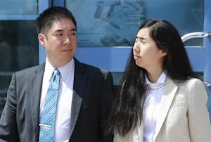 Matthew and Grace Huang, a U.S. couple who were accused of murdering their adopted daughter Gloria, stand outside the entrance of the Court of First Instance after their trial in Doha