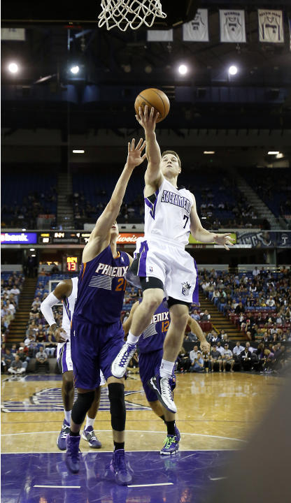 Sacramento Kings guard Jimmer Fredette, right, drives to the basket against Phoenix Suns center Alex Len, left, during the fourth quarter of an NBA preseason basketball game in Sacramento, Calif., Thu