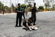 Forensic policemen collect evidence at the site of a suicide bomb attack in Sanaa on Monday. The suicide attack was the deadliest in the country&#39;s capital since newly-elected President Abdrabuh Mansur Hadi pledged to oust Al-Qaeda militants from Yemen&#39;s mostly lawless and restive southern and eastern provinces