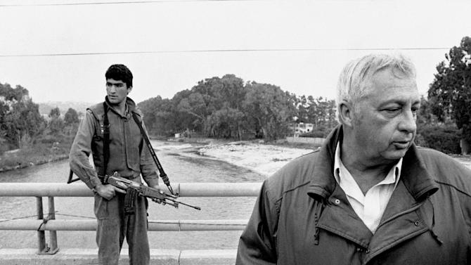 FILE - In this March 7, 1984 file photo, an Israeli soldier keeps his finger on the trigger of his assault rifle while Former Defense Minister Ariel Sharon, right, stands on the bridge overlooking the Awali River, Israel's most northerly position in Sidon, Lebanon. Sharon, the hard-charging Israeli general and prime minister who was admired and hated for his battlefield exploits and ambitions to reshape the Middle East, died Saturday, Jan. 11, 2014. The 85-year-old Sharon had been in a coma since a debilitating stroke eight years ago. (AP Photo/Max Nash, File)