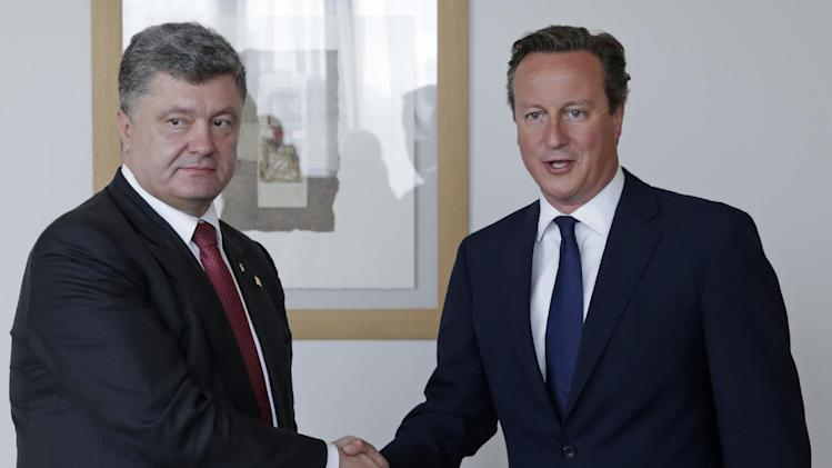 Ukrainian President Petro Poroshenko, left, shakes hands with British Prime Minister David Cameron, prior to a bilateral meeting, ahead of an EU summit in Brussels, Saturday, Aug. 30, 2014. EU leaders, in a one day summit, are set to decide who will get the prestigious job as the 28-nation bloc's foreign policy chief for the next five years. They will also discuss the current situation in Ukraine. (AP Photo/Yves Logghe, Pool)