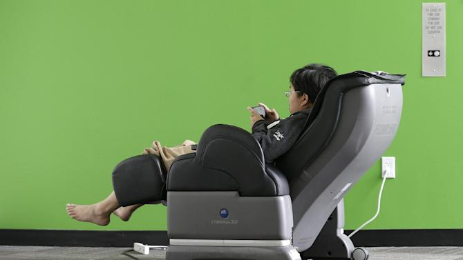 Google software engineer Jiang Chen campus sits in a massage chair at a Google campus building in Mountain View, Calif., Friday, March 15, 2013. Companies say extraordinary campuses are a necessity, to recruit and retain top talent, and to spark innovation and creativity in the workplace. And there are business benefits and financial results for companies that keep their workers happy. (AP Photo/Jeff Chiu)