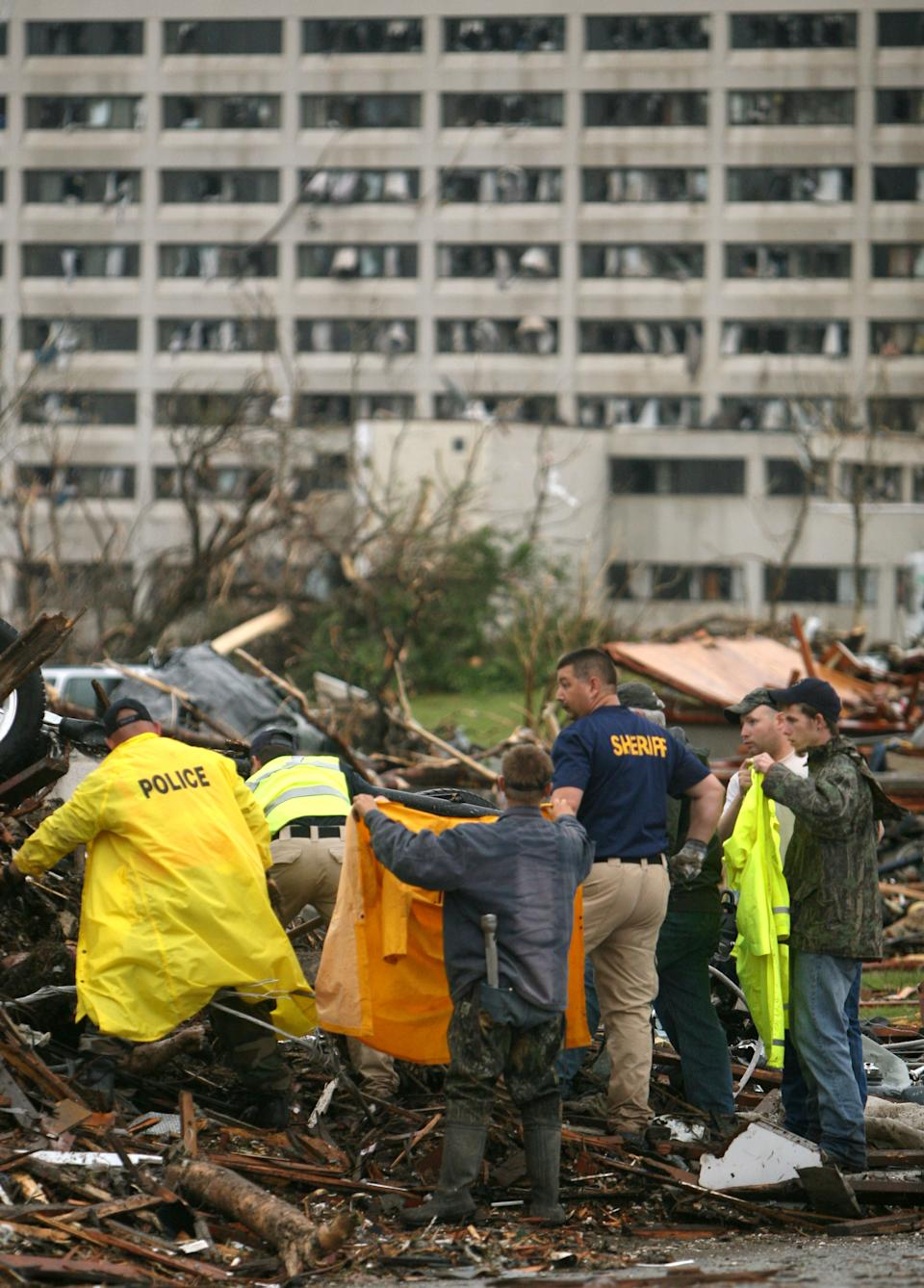 Emergency personnel excavate a body from the wreckage of a home near the St. John's Regional Medical Center in Joplin, Mo., Monday, May 23, 2011. A destructive tornado moved through the city on Sunday evening, killing at least 89 people and injuring hundreds more. (AP Photo/Mark Schiefelbein)