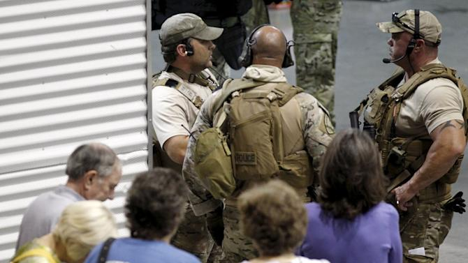 Police officers stand guard at an entrance as attendees are prevented from leaving the Muhammad Art Exhibit and Contest after shots were fired outside the venue in Garland, Texas