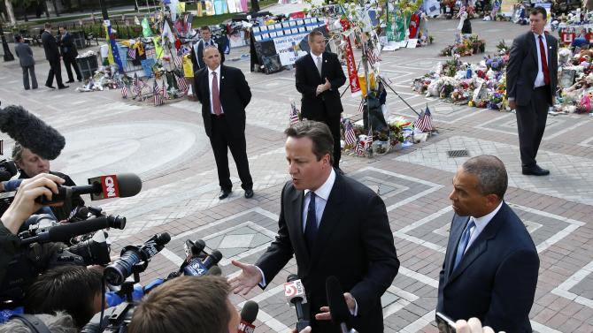 British Prime Minister David Cameron, center, speaks to the media as Massachusetts Gov. Deval Patrick, right, listens during a visit at the makeshift memorial to the Boston Marathon bombing victims in Copley Square in Boston, Tuesday, May 14, 2013. Cameron is in Boston to offer his condolences and discuss lessons that can be learned from the deadly bombings. (AP Photo/Michael Dwyer)