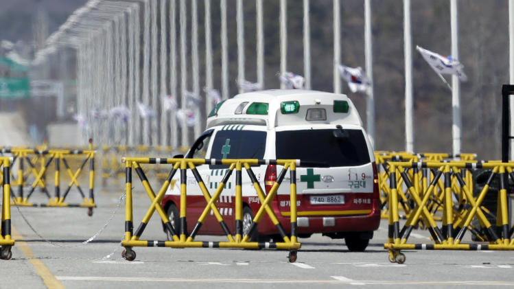 An ambulance drives through barricades on the Unification Bridge near the border village of Panmunjom, that has separated the two Koreas since the Korean War, in Paju, north of Seoul, South Korea, Sunday, April 7, 2013. South Korea said its top military officer has put off a plan to visit Washington due to current tension with North Korea. (AP Photo/Lee Jin-man)