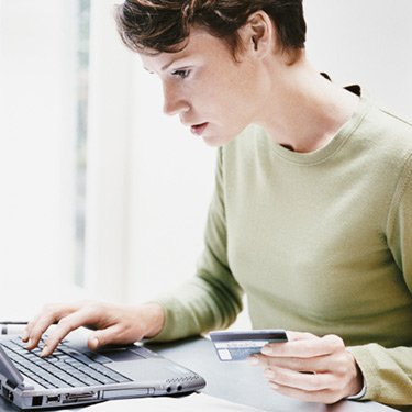Woman-sits-at-a-desk-using-a-laptop-and-paying-a-bill-online-with-her-credit-card_web