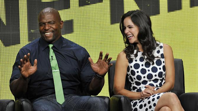 """FILE - In this Aug. 1, 2013 photo, Terry Crews, left, and Melissa Fumero, cast members in the FOX series """"Brooklyn Nine-Nine,"""" share a laugh onstage during the FOX 2013 Summer TCA press tour at the Beverly Hilton Hotel, in Beverly Hills, Calif. Fox says the plum post-Super Bowl slot next February will be filled by two of its comedies. """"New Girl"""" and freshman series """"Brooklyn Nine-Nine"""" will air on Fox after the game that's typically TV's most-watched program and a big promotional platform for other network fare. (Photo by Chris Pizzello/Invision/AP, File)"""