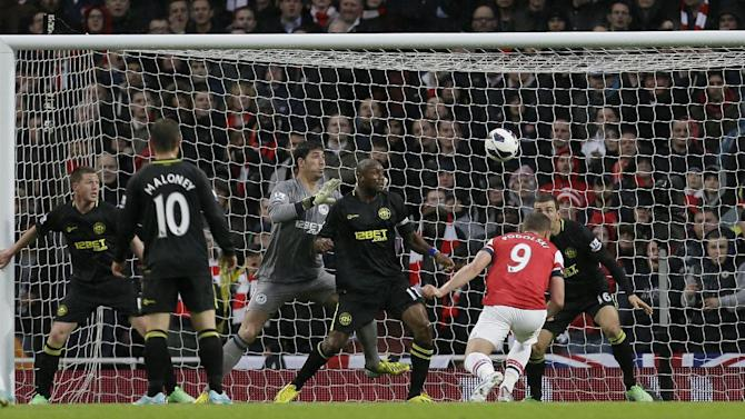 Arsenal's Lukas Podolski, No. 9, second right, heads the ball to score a goal against Wigan Athletic during their English Premier League soccer match at Arsenal's Emirates stadium in London, Tuesday, May  14, 2013. (AP Photo/Alastair Grant)