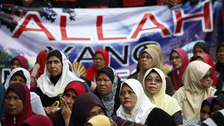"""Muslim women sit in front of a banner reading """"Allah"""""""