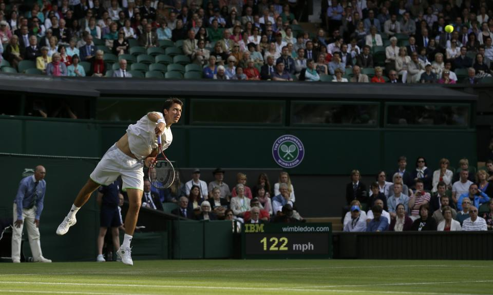 Sergiy Stakhovsky of Ukraine serves to Roger Federer of Switzerland during their Men's second round singles match at the All England Lawn Tennis Championships in Wimbledon, London, Wednesday, June 26, 2013. (AP Photo/Alastair Grant)