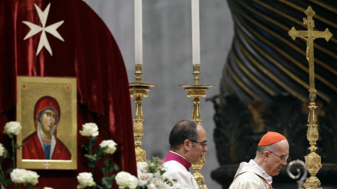 Cardinal Tacisio Bertone, right, celebrates a mass to mark the 900th anniversary of the Order of the Knights of Malta, at the Vatican Saturday, Feb. 9, 2013. The order traces its history to the 11th century with the establishment of an infirmary in Jerusalem that cared for people of all faiths making pilgrimages to the Holy Land. It is the last of the great lay chivalrous military orders like the Knights Templars that combined religious fervor with fierce military might to protect and expand Christendom from Islam's advance during the Crusades. In February 1113, Pope Paschal II issued a papal bull recognizing the order as independent from bishops or secular authorities, reason for Saturday's anniversary celebrations at the Vatican. (AP Photo/Gregorio Borgia)