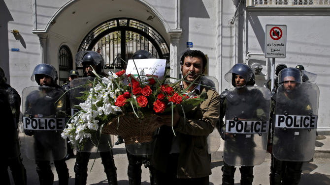 """An Iranian student holds bouquet of flowers with a verse from the Holy Quran in Arabic that reads,""""do not fight, or you may fail, and your strength and willpower will weaken,"""" is seen, as police stand guard, background, during a rally in support of solidarity with Egypt, in Tehran, Iran, Tuesday, April 9, 2013. Last week, a group of angry ultraconservative Salafis protesters threw rocks and tried to storm the residence of Iran's top diplomat in Cairo, after Iranian tourists arrived in Egypt on the first commercial flights between the two countries in 30 years. (AP Photo/Ebrahim Noroozi)"""