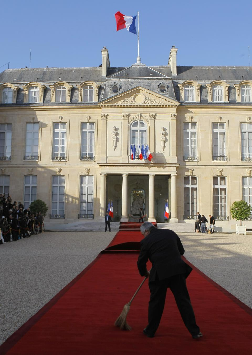 A worker prepares the red carpet for the takeover ceremony between outgoing President Nicolas Sarkozy and President-elect Francois Hollande, Tuesday, May 15, 2012, at the Elysee Palace in Paris.  (AP Photo/Jacques Brinon)