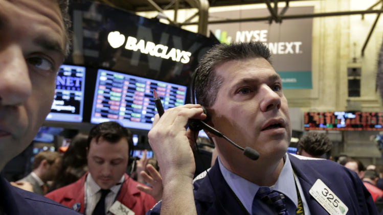 Trader William McInerney, right, works on the floor of the New York Stock Exchange, Friday, April 12, 2013. The stock market is heading lower in early trading after a four-day rise as bank shares weaken. (AP Photo/Richard Drew)