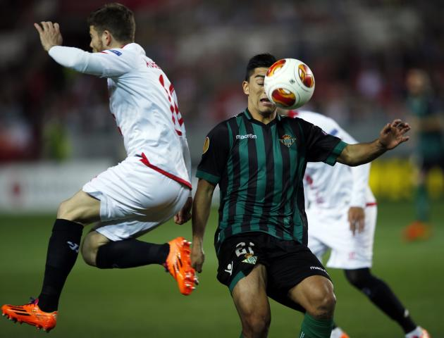 Sevilla's Alberto Moreno jumps past Real Betis' Lorenzo Reyes during their Europa League soccer match in Seville