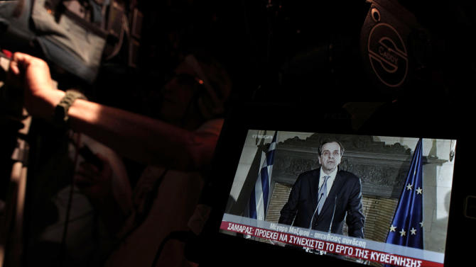 Greek Prime Minister Antonis Samaras is seen in the monitor of a TV crew outside his central Athens office during a live address to the nation early Friday, June 21, 2013. Samaras said he's determined to avoid early elections despite a deep rift with a coalition ally, which threatened new political instability in the bailed-out country and prompted warnings from international creditors. (AP Photo/Petros Giannakouris)