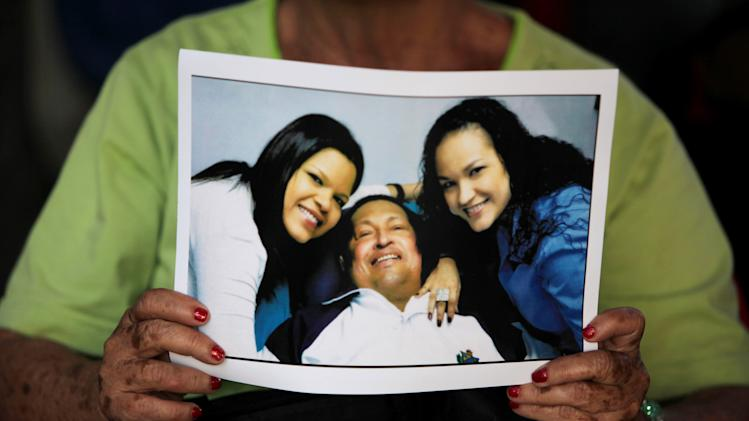 """FILE - In this Feb. 15, 2013 file photo, a woman holds a newly purchased copy of  a photo released by the government, showing Venezuela's President Hugo Chavez at the hospital in Havana, with two of his daughters, in Caracas,Venezuela. Venezuela's government said that President Hugo Chavez's respiratory problems have gotten worse and that the ailing leader is in """"very delicate"""" condition. Communications Minister Ernesto Villegas said late Monday March 4, 2013 in a statement read on national television that Chavez has a """"severe infection."""" The 58-year-old Chavez first revealed an unspecified cancer in the pelvic region in June 2011, and reported undergoing radiation treatment and chemotherapy after earlier operations. He underwent cancer surgery in Cuba on Dec. 11 and flew back to Caracas on Feb. 18.(AP Photo/Fernando Llano, File)"""