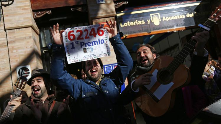 "People sing as they show a poster of the winning number to the first prize of ""El Gordo"" outside a lottery shop where the lottery number was sold in Sanlucar la Mayor"