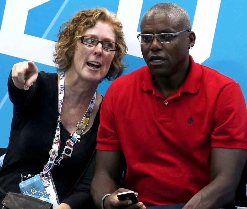 Olympic gold medalist Carl Lewis, right, sits with actress Susan Sarandon during a preliminary men's water polo match between Italy and Spain at the 2012 Summer Olympics, Monday, Aug. 6, 2012, in London. (AP Photo/Julio Cortez)