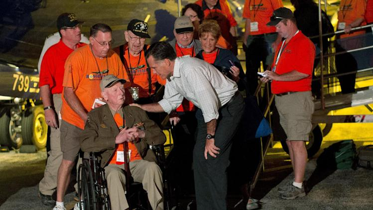 FILE - In this Sept. 26, 2012, file photo Republican presidential candidate, former Massachusetts Gov. Mitt Romney shakes hands with World War II and Korean War veterans returning on an Honor Flight from Washington in Swanton, Ohio. Romney's road team scrambled to set up an impromptu meet-and-greet when his plane landed in Ohio at about the same time as an honor flight of aging veterans just back from visiting Washington memorials. Every day, the ground troops of Team Obama and Team Romney set out in pursuit of a common goal: winning the day. Everyone poses for the camera.  (AP Photo/ Evan Vucci, File)
