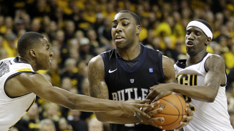 Butler forward Roosevelt Jones (21) tries to break free as Virginia Commonwealth guards Briante Weber, right, and Rob Brandenberg, left, defend during the second half of an NCAA college basketball game in Richmond, Va., Saturday, March 2, 2013.  VCU won 84-52.  (AP Photo/Steve Helber)