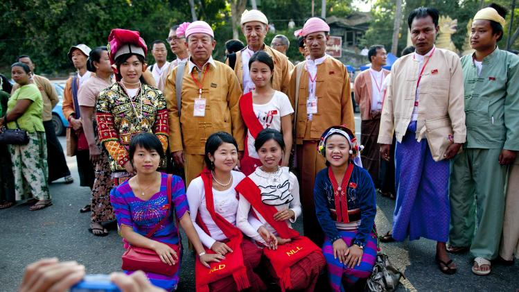 "Ethnic Shan representatives of Aung San Suu Kyi's National League for Democracy, with badges around their necks, pose for photos with women dressed in ethnic attire outside the venue of first ever NLD party congress in Yangon, Myanmar, Friday, March 8, 2013. Nearly 900 representatives from across the country stood in neat lines outside the Taw Win (""Royal Rose"") restaurant, waiting to be screened for entry to elect their party leadership for the first time in the NLD's 25-year history. (AP Photo/Gemunu Amarasinghe)"