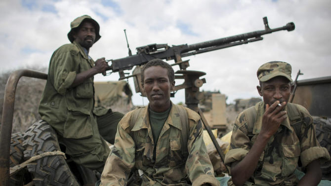 In this photo released by the African Union-United Nations Information Support Team, soldiers of the Somali National Army (SNA) sit on their vehicle in Saa'moja, around 7km north-west of the port city of Kismayo, in southern Somalia, Monday, Oct. 1, 2012. Residents in the southern Somali port city of Kismayo say Somali troops have entered the city for the first time since Kenyan troops carried out an amphibious assault on the coastal port city last week, causing al-Shabab militants to flee. (AP Photo/AU-UN IST, Stuart Price)