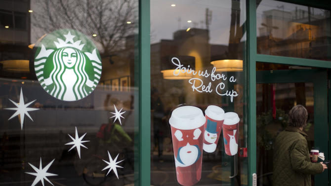 "A man walks out of a Starbucks coffee cafe holding a drink in west  London, Monday, Dec.  3, 2012.   A committee of British lawmakers says the government should ""get a grip"" and clamp down on multinational corporations that exploit tax laws to move profits generated in Britain to offshore domains.The committee says major multinationals including Starbucks, Google and Amazon are guilty of immoral tax avoidance. Starbucks announced it is reviewing its British tax practices in a bid to restore public trust. (AP Photo/Alastair Grant)"