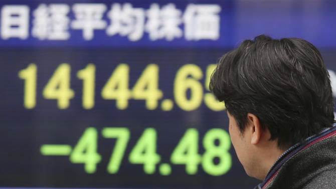 A man looks at an electronic stock board of a securities firm in Tokyo, Tuesday, Feb. 4, 2014. Weakness in U.S. and Chinese manufacturing sent Asian stock markets sharply lower Tuesday. (AP Photo/Koji Sasahara)