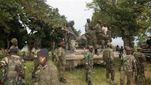 Congolese soldiers pose on a tank to celebrate their victory after taking over the headquarters of the M23 rebels at Rutshuru, north of Goma