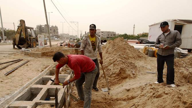 In this Monday, April 8, 2013 photo, Palestinians work on a Qatar-funded road in Gaza City. The newly re-elected leader of Hamas, Khaled Mashaal, is expected to strengthen ties with Qatar, Egypt and Turkey in his next four-year term. (AP Photo/ Hatem Moussa)