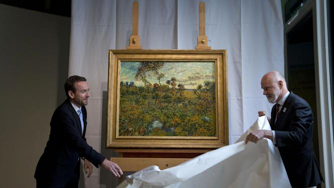 """CAPTION CORRECTION, CORRECTS SPELLING OF SURNAME TO REFLECT AP STYLE - Van Gogh Museum director Axel Rueger, left, and senior researcher Louis van Tilborgh, right, unveil """"Sunset at Montmajour"""" during a press conference at the Van Gogh Museum in Amsterdam, Netherlands, Monday Sept. 9, 2013. The museum has identified the long-lost painting which was painted by the Dutch mater in 1888, the discovery is the first full size canvas that has been found since 1928 and will be on display from Sept. 24. (AP Photo/Peter Dejong)"""