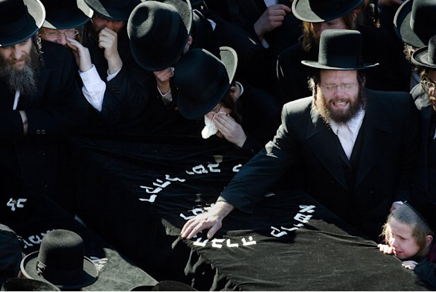 Members of the Satmar Orthodox Jewish community grieve over the coffins at the funeral for two expectant parents who were killed in a car accident, Sunday, March 3, 2013, in the Brooklyn borough of Ne