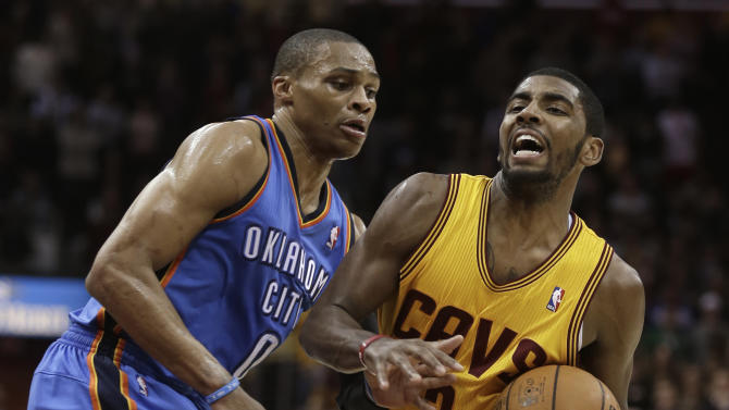 Cleveland Cavaliers' Kyrie Irving, right, drives to the basket against Oklahoma City Thunder's Russell Westbrook (0) during the fourth quarter of an NBA basketball game on Saturday, Feb. 2, 2013, in Cleveland. Irving scored a team-high 35 points for the Cavaliers' 115-110 win. (AP Photo/Tony Dejak)