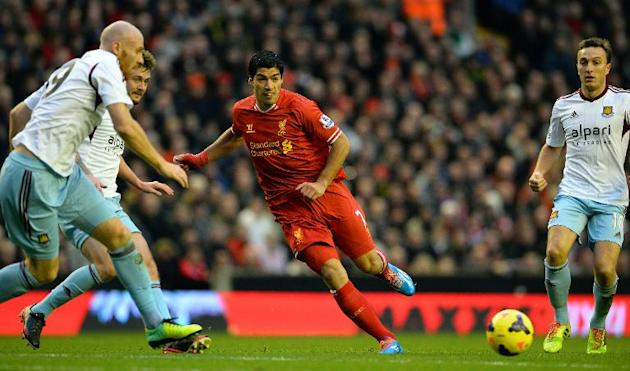 Liverpool's Uruguayan striker Luis Suarez (2nd R) runs with the ball during the English Premier League football match between Liverpool and West Ham United at Anfield in Liverpool on December 7, 2
